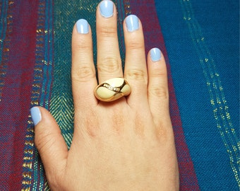 Gold plated ring with beige finished details.