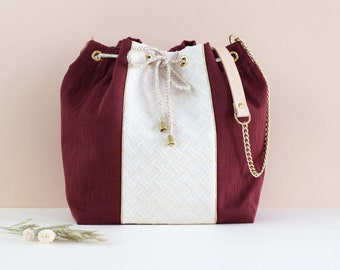 Denise: bucket bag made of  and off-white cotton, lurex piping and golden chain.