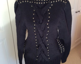 black hand knit sweater in wool medium size with wide cables and brass metal beading side mock pockets long length