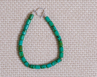 Beaded bracelet of green turquoise with dark matrix. Barrel -shaped turquoise, sterling silver toggle clasp