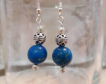 A silver drop earring with a blue-green earthy stone
