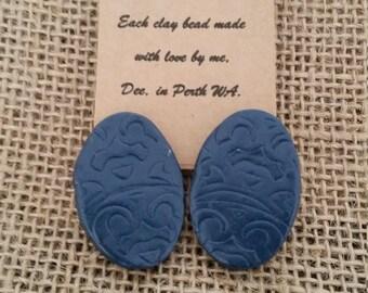 Navy medium+ oval stud imprinted earrings.