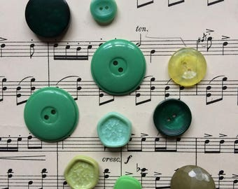 Assortment of eleven green plastic flat backed and shank buttons