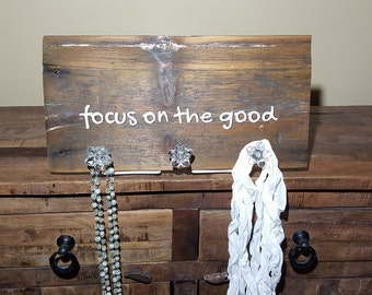 Barnwood plank with clear floral knobs 'focus on the good'