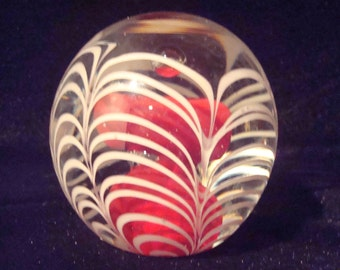 Hollowblown red paperweight with white swirls