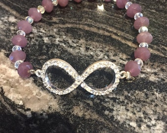 Infinity stretch bracelet with plum and clear colored crystals. Handmade