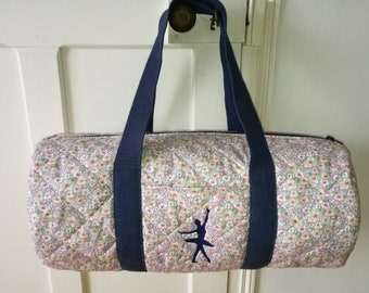 Fabric with embroidery quilted duffel bag.