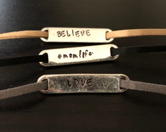 Hand stamped metal band bracelet with faux suede cord