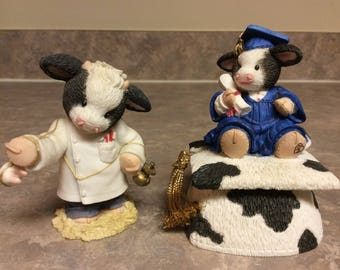 """Two Mary's Moo Moos, """"Cowgraduations"""" and """"Don't Mooove... This Won't Hurt A Bit"""" Figurines."""