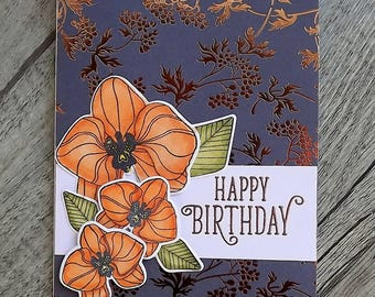 Birthday card with dark foiled background and hand coloured orchids, with heat embossed sentiment