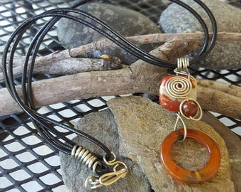 Nickel silver pendant two red jasper plus,  an agate bead on a black leather cord.