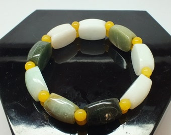 Vintage Jadeite bracelets - elastic , cold and heavy with transition beads of yellow serpentine