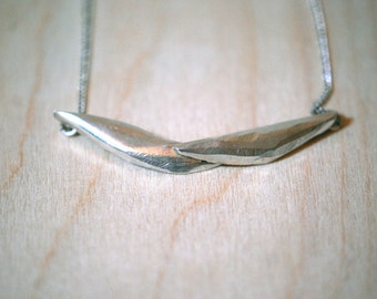Silver necklace with two overlapping petals.