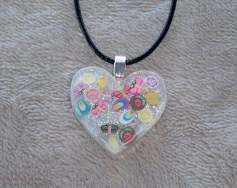 Pretty little handmade resin heart charm necklace with tiny butterflies, dragonflies, petals and glitter