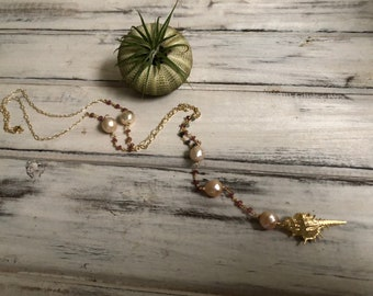 Gold triton shell lariat necklace featuring a Edison pearls and tourmaline rosary