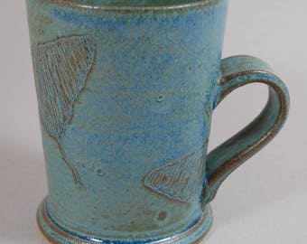 Stoneware coffee cup with ginko leaf decorations