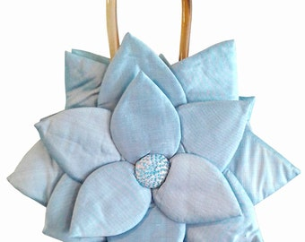 Pretty flower purse. Handheld purse made of light blue satin fabric. Lining is also blue satin. Tiny beadwork accents the flower center.