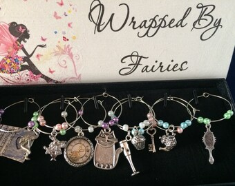 Alice in Wonderland Themed Wine Glass Charms. Sold in silver storage box.