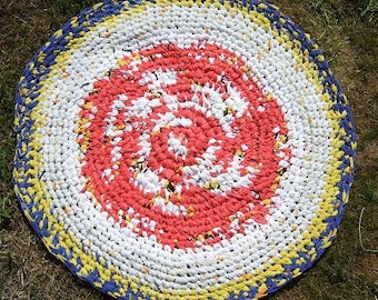 Rag rug made of upcycled cotton. Colours red-white-black-yellow-blue. Diameter abt 84 cm