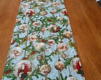 """TRC-20   72""""X14""""   Nostalgic & beautiful Christmas table runner featuring bulbs of olde-world Santa's and Angels."""