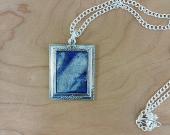 Necklace: blue + silver framed pendant on silvery chain; gift for her