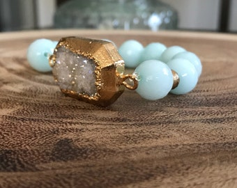 Gold plated large white druzy with 12 mm aquamarine gemstone with gold spacer bracelet .