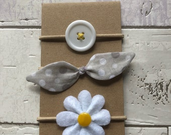 Trio of elastic with button, loop and beige felt flower.
