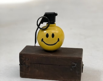 Hand painted smiley face hand grenade.
