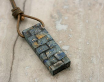 Polymer clay over wood on leather necklace. E.