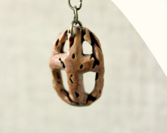 cross necklace whittled by hand out of a peach seed