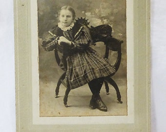 Antique photograph cabinet card girl child in plaid dress sitting on chair from 1897