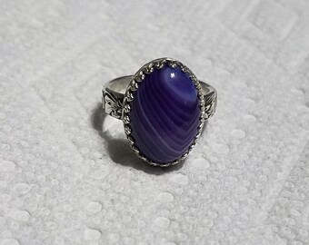 This ring is a Purple Onyx Agate ( 13 x 18 mm ) size 7 3/4. It is set in a gallery bezel. The stone is one of a kind.