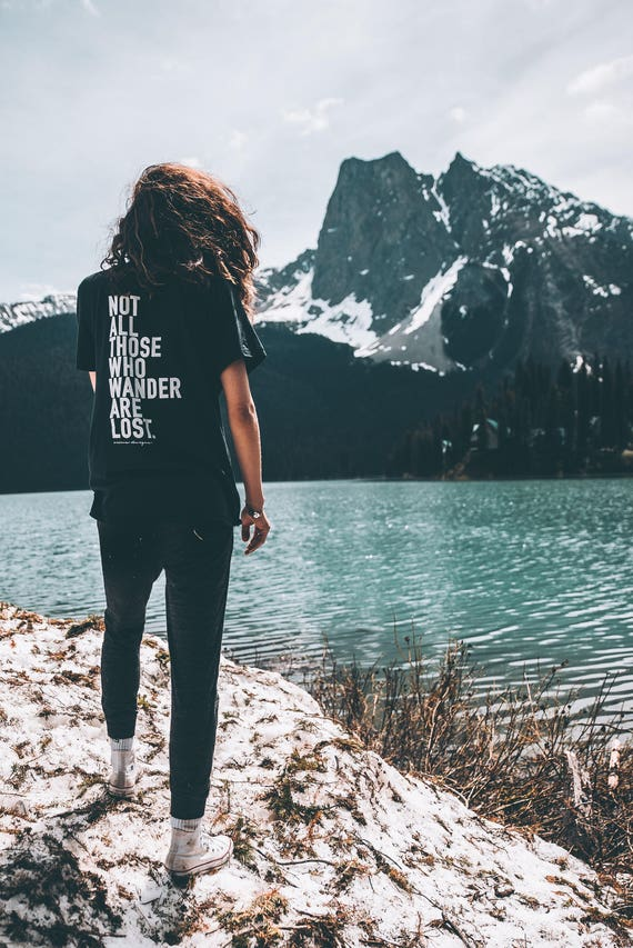 girl in wander tee overlooking lake and mountains