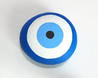 Evil  Eye Hand Painted Pebble! Is hand painted on a smooth pebble with Acrylic paints and covert with glossy varnish protection