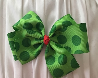 Two-tone green polka-dot pinwheel bow.