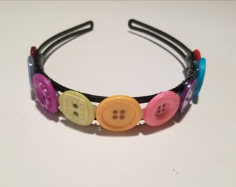 Black plastic headband adorned with colorful decorative buttons