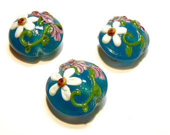 One (1) Teal Blue Puffy Lampwork Lentil Bead with Purple and White Flower Design - Lot UU