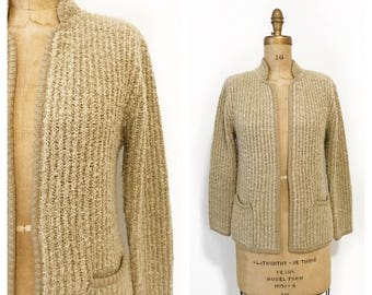 Cream ribbed acrylic knit cardigan with front pockets. Size M.