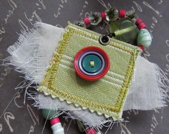 Asymétrique collier vert avec Repurposed Textile tissu bouton rouge pendentif