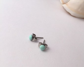 New improved waterproof design! Itty bitty, mint green, eco-resin studs on allergy-friendly surgical steel.