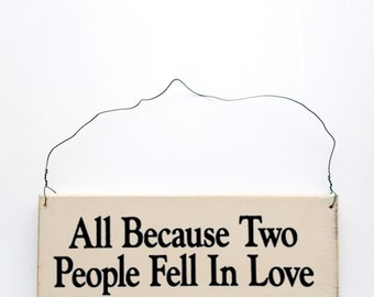 Wood sign saying: All Because Two People Fell In Love