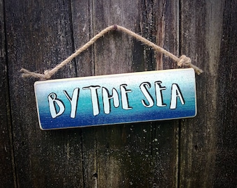 Handmade wooden sign with the words 'by the sea'.