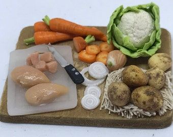 One inch scale chicken breast fillets and vegetables on a wooden preparation board.