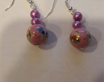Pink ball with flower on it with 2 purple beads on top