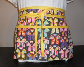 Waitress/utility/vendor apron with 3 large pockets. Bright, colorful, sunny butterflies on a brown background with yellow trim.