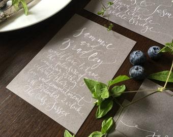Handwritten calligraphy invitation on grey card