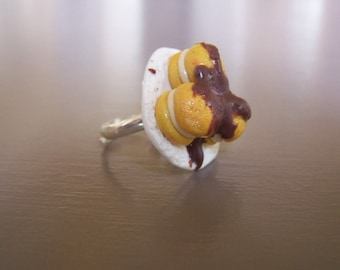Ring profiteroles deposited on a small plate, dessert jewelry greedy kawai Chocolate sculpture food.
