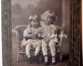 Way cute little sisters love each other, posed for camera with Doll Circa 1910