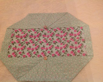 A lovely dainty print floral placemat. It features little red roses on a green background