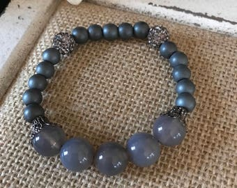 Gray 8mm and 10mm beaded bracelet with metal accents.